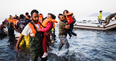 Locals carry two young girls to the shores of Lesbos, after they reached the island with their families in an inflatable boat full of refugees and migrants, having crossed the Aegean sea from Turkey.